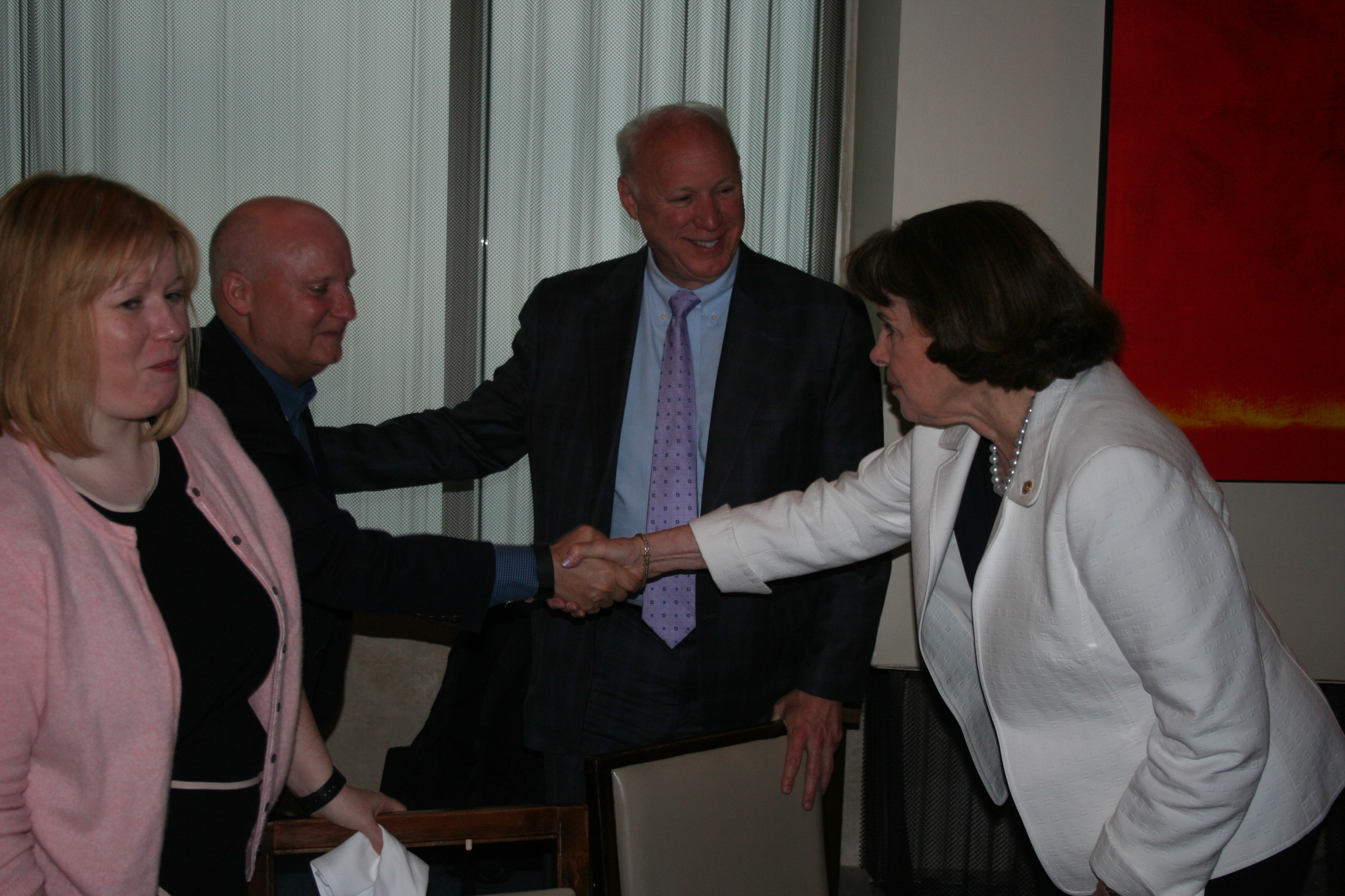 Sen. Dianne Feinstein, then the ranking member of the Senate Intelligence Committee, shakes the hand of board member JR Williamson, Northrop Grumman Corporate Chief Information Officer