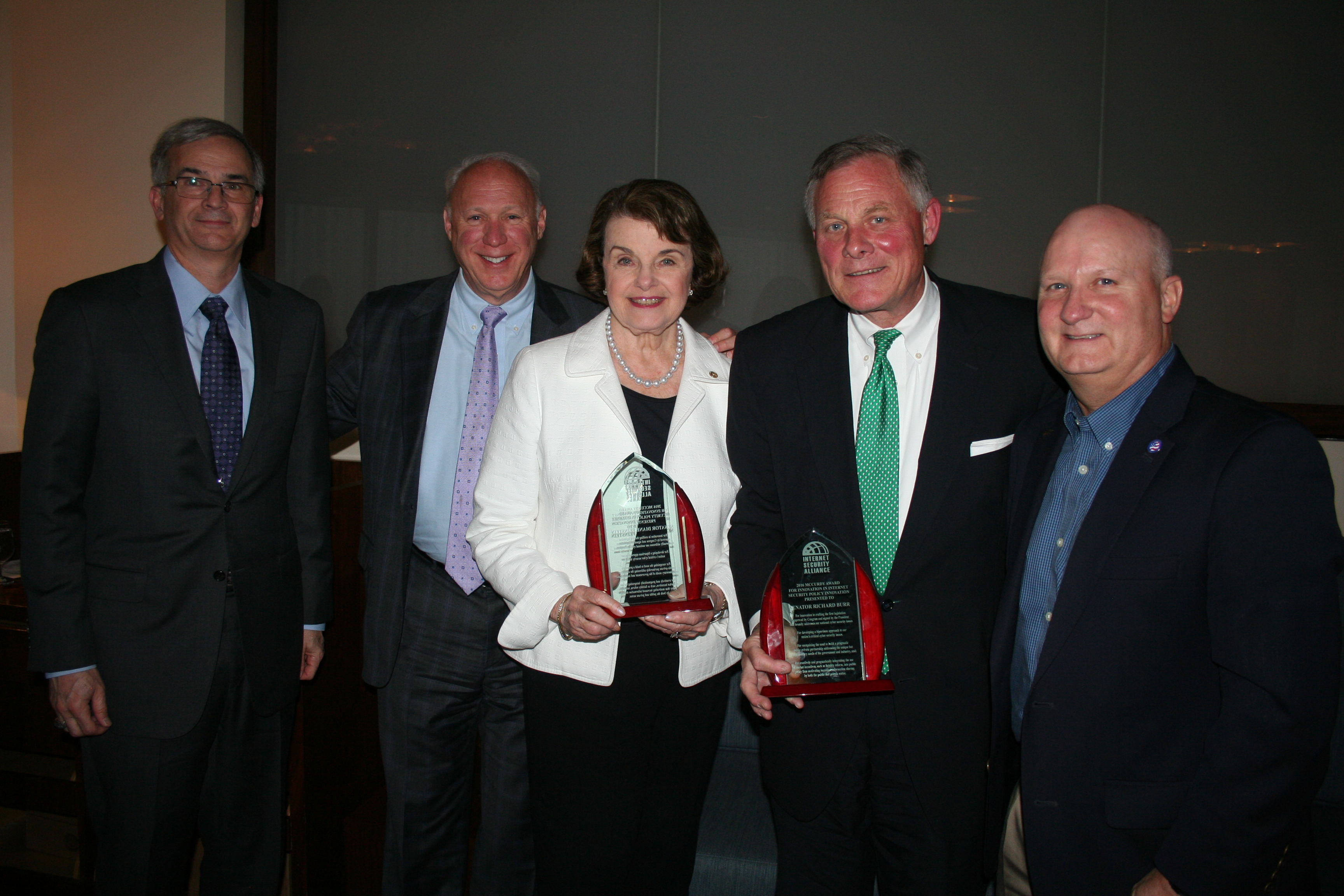 Senate Intelligence Committee Chairman Richard Burr (center left) and Ranking Member Dianne Feinstein (center right) receive the McCurdy Award in 2016. At far right is ISA board member JR Williamson (Northrop Grumman). At extreme left are ISA board members Jeff Brown (Raytheon) and Larry Clinton (ISA).